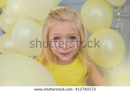 Portrait of a beautiful little girl in a yellow dress with a yellow balloons - stock photo