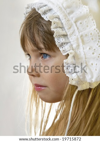 Portrait of a beautiful little girl in old -fashioned lace cap, side view