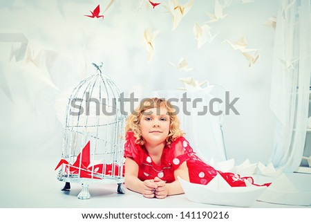 Portrait of a beautiful little girl lying on a floor with her birdcage with a red paper bird. - stock photo