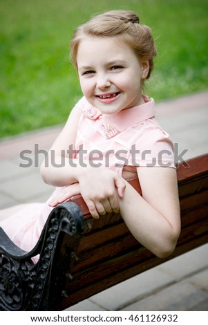 Portrait of a beautiful little girl sitting on a Park bench