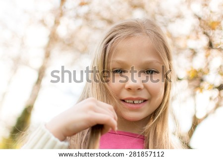 Portrait of a Beautiful little girl with blue eyes in the park. Looking at camera.