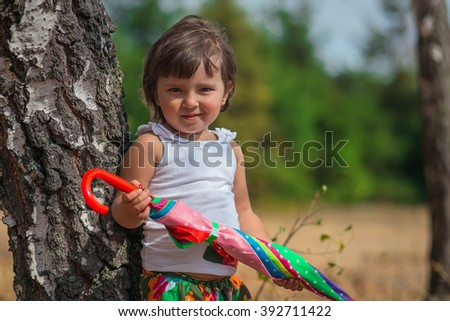 portrait, of a beautiful little girl with umbrella near birch. lovely sunny day in the forest - stock photo