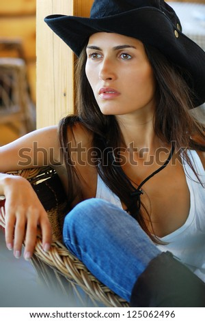 Portrait of a beautiful long-haired country style woman in black hat and jeans sitting in a wicker chair - stock photo