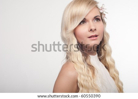 Portrait of a beautiful  longhair blonde woman with  natural make-up on grey background