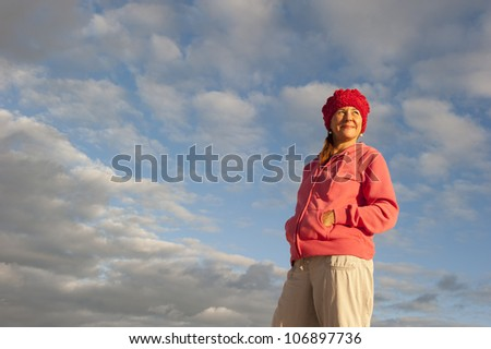 Portrait of a beautiful looking middle aged woman in casual pose, wearing pink sweater and red cap, with soft sunlight on her face and picturesque cloudscape as background and copy space. - stock photo