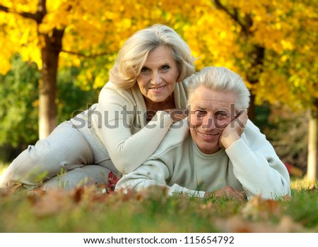 portrait of a beautiful mature couple lying on the autumn leaves