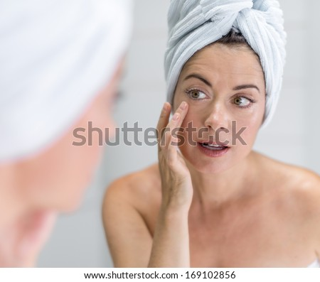 portrait of a beautiful mature lady with a towel on her head looking at her skin in the mirror - stock photo