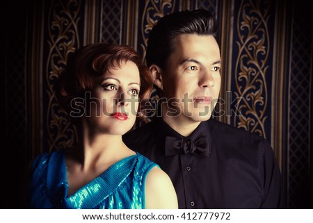 Portrait of a beautiful mature man and woman in evening clothes over vintage background. - stock photo