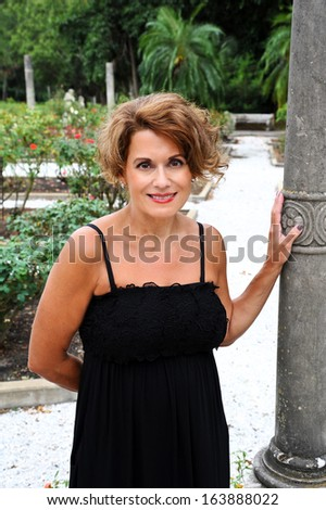 Portrait of a Beautiful Mature Woman in the Garden - stock photo