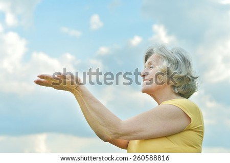 Portrait of a beautiful mature woman on the background of sky - stock photo