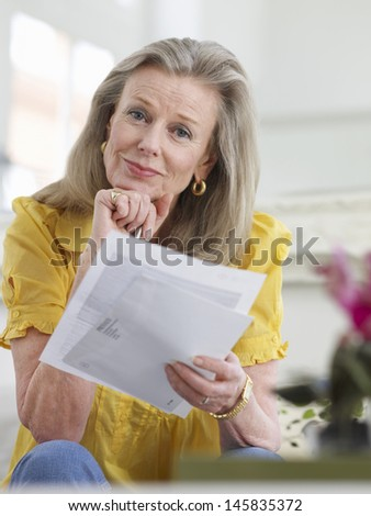 Portrait of a beautiful mature woman reading documents at home - stock photo