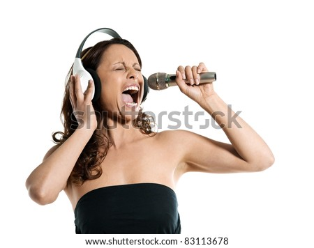 Portrait of a beautiful mature woman singing into microphone with headphones in studio isolated on white background - stock photo