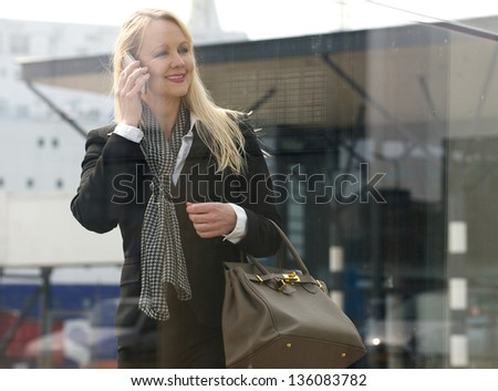 Portrait of a beautiful mature woman talking on mobile phone outdoors - stock photo