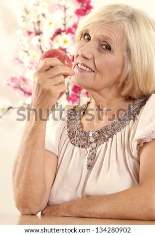 portrait of a beautiful mature woman with ripe apple