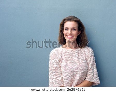 Portrait of a beautiful mid adult woman smiling on blue background - stock photo