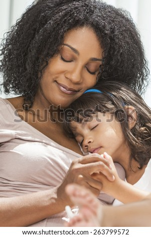 Portrait of a beautiful middle aged African American woman at home relaxing resting sleeping with her female child daughter - stock photo