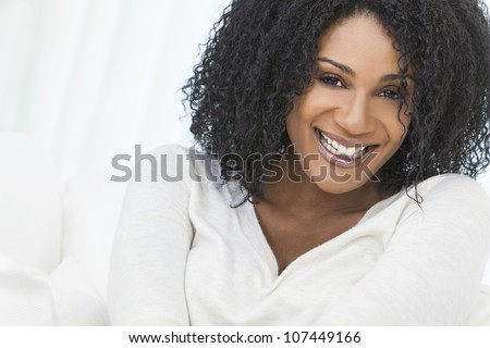 Portrait of a beautiful middle aged African American woman sitting at home relaxing smiling or laughing - stock photo