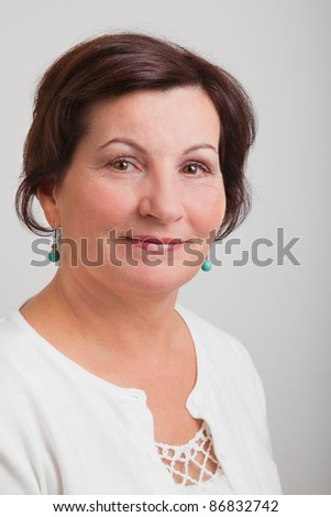Portrait of a beautiful middle aged woman against a gray background. - stock photo