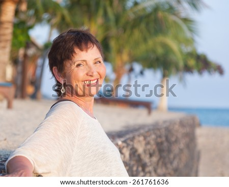 portrait of a beautiful middle-aged woman on the beach - stock photo