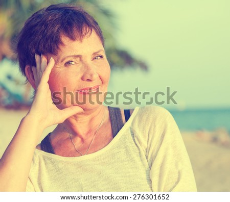 portrait of a beautiful middle-aged woman on the beach. Image with retro toning - stock photo