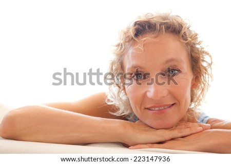 Portrait of a beautiful middle aged woman sitting down and relaxing on a white sofa at home, turning to the camera and smiling indoors. Home living and relaxing well being lifestyle interior. - stock photo