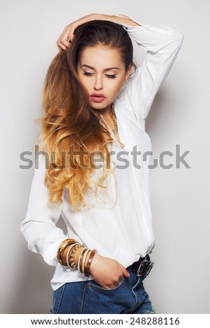 Portrait of a Beautiful model with long curly brown hair. Pretty girl poses at studio. Portrait of the beautiful young fashionable girl in studio posing against white wall. Portrait of beautiful woman - stock photo