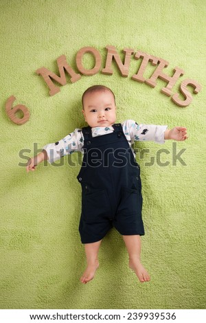Portrait of a beautiful 6 months baby smiling. Top view of asian child. Age concept - stock photo