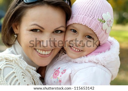 portrait of a beautiful mother and a little girl in the autumn - stock photo