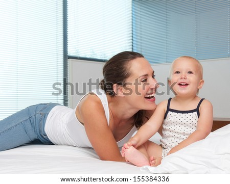 Portrait of a beautiful mother laughing with cute baby in bed