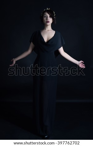 Portrait of a beautiful mysterious woman, red lipstick and collar with beads - stock photo