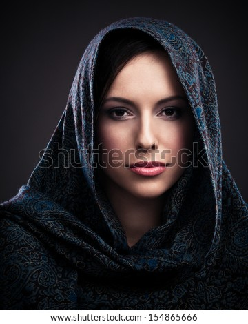 Portrait of a beautiful mysterious woman wearing a headscarf. - stock photo