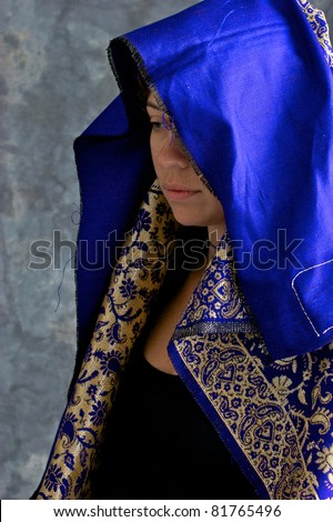 Portrait of a beautiful mystical woman in profile, looking down, her head is covered with blue hood and looks thoughtful. - stock photo