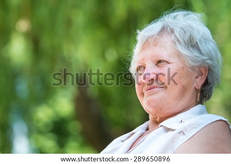 Portrait of a beautiful pensioner on nature background - stock photo