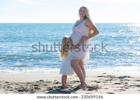 Portrait of a beautiful pregnant woman and daughter on sea background