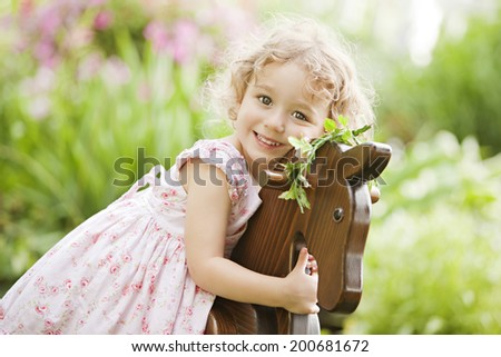 Portrait of a beautiful preschooler out in the garden on a wooden rocking horse. - stock photo