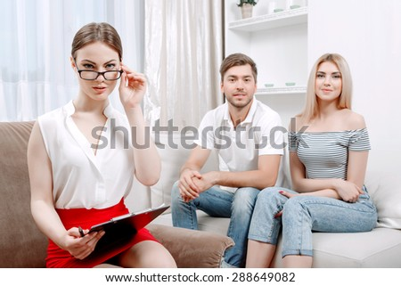 Portrait of a beautiful psychologist wearing white blouse and black skirt touching her glasses sitting at her office during therapy session, patients young couple on a couch smiling, selective focus - stock photo