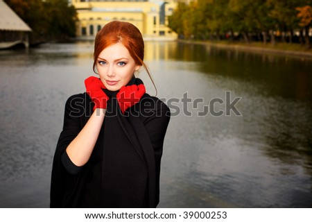 Portrait of a beautiful red-haired woman in red gloves - stock photo