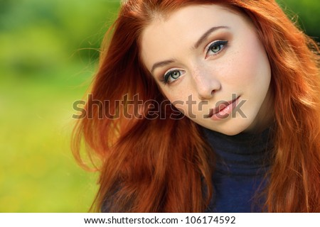 Portrait of a beautiful red-haired young woman outdoors. - stock photo