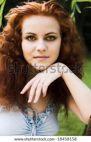 Portrait of a beautiful red-headed girl in forest - stock photo