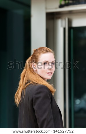 Portrait of a beautiful redhead businesswoman at the entrance of the office