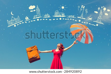 Portrait of a beautiful redhead girl in red dress with suitcase and umbrella  - stock photo