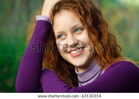 Portrait of a beautiful redhead girl smiling outdoors - stock photo