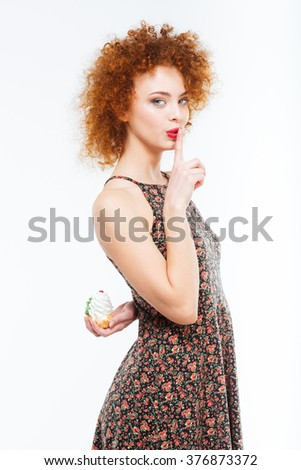 Portrait of a beautiful redhead woman holding cake and showing finger over lips isolated on a white background