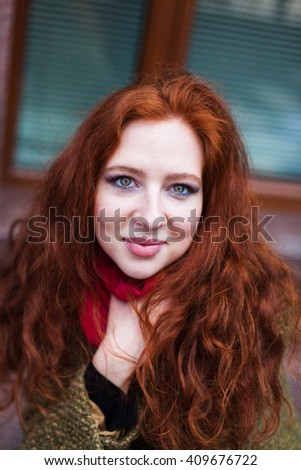 Portrait of a beautiful redhead woman in pink scarf and green coat, closeup, cute - stock photo