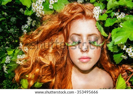 Portrait of a beautiful redhead woman with freckles, wavy long hair and fantasy makeup, framed by green foliage and white flowers at background - stock photo