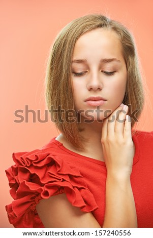 Portrait of a beautiful sad woman in red dress on pink background