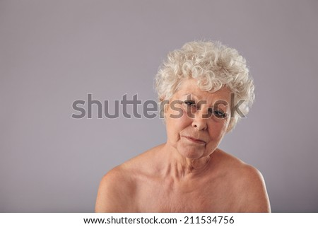 Portrait of a beautiful senior woman looking serious. Shirtless old lady looking sad with copy space on grey background. - stock photo