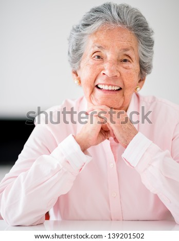 Portrait of a beautiful senior woman smiling at home - stock photo