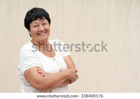 Portrait of a beautiful senior woman with a warm friendly smile and attentive expression. Light wall as a background.  - stock photo