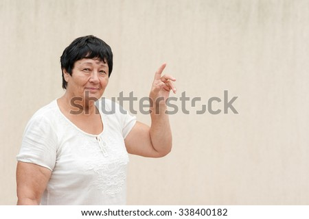 Portrait of a beautiful senior woman with a warm friendly smile and attentive expression. Light wall as a background. The woman raised a hand and points a finger up.  - stock photo